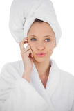 Content brunette in bathrobe looking away Stock Photography