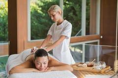 Content brunette enjoying a herbal compress massage Stock Photos