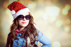 Content brunette female in Christmas hat and Stock Photos