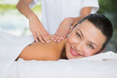 Content brunette getting a back massage smiling at camera Stock Photo