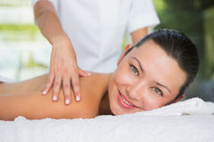 Content brunette getting a back massage smiling at camera Stock Photos