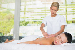 Content brunette getting a back massage Royalty Free Stock Image