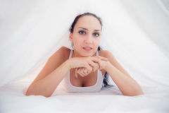 Content brunette lying under the sheets smiling at camera Stock Images