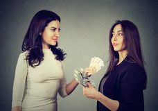 Content business women exchanging money. Young serious models carrying on trade and exchanging with money posing on gray stock photo