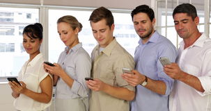 Content businesspeople text messaging while standing in a row Royalty Free Stock Photography