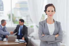 Content businesswoman posing while her colleagues are working. In bright office stock photography