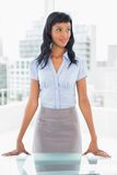 Content businesswoman standing at her desk Stock Images