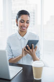 Content businesswoman using a calculator sitting at her desk Royalty Free Stock Image