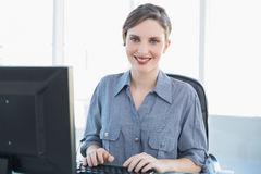 Content businesswoman working on computer at her desk Royalty Free Stock Photography