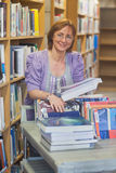 Content calm female librarian returning books. Smiling at camera Royalty Free Stock Photo