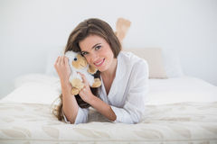 Content casual brown haired woman in white pajamas hugging a plush sheep Royalty Free Stock Image
