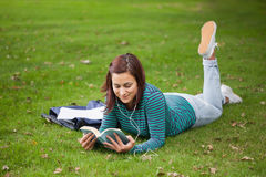Content casual student lying on grass reading Royalty Free Stock Photography