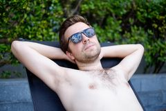 Content caucasian man in a swimming pool. He is enjoying his time during vacation in summer Royalty Free Stock Image