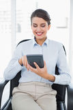 Content classy brown haired businesswoman using a calculator. In bright office Stock Photos