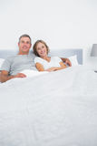 Content couple cuddling in bed looking at camera Stock Images