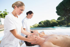 Content couple enjoying head massages poolside Stock Images