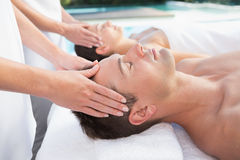Content couple enjoying head massages poolside Royalty Free Stock Image