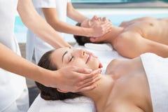 Content couple enjoying head massages poolside Stock Image