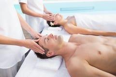 Content couple enjoying head massages poolside Stock Photos