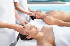 Content couple enjoying head massages poolside Royalty Free Stock Photography