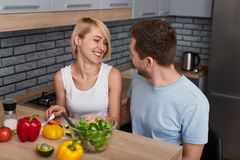 Content couple preparing vegetable salad together royalty free stock photography
