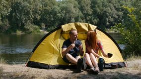Content happy couple sitting in tent. Concept of tourism and travel. The girl pours tea from a thermos. Forest and river. Content couple sitting in tent. Concept stock video footage