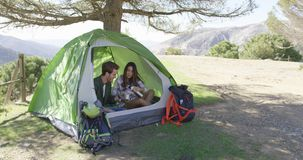 Content couple sitting in tent under trees. Young happy couple taking rest in tent under trees with mountains on background stock video
