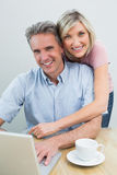 Content couple using laptop at home Stock Photography