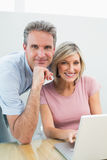 Content couple using laptop at home Stock Images