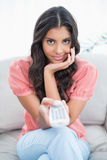 Content cute brunette sitting on couch holding remote Royalty Free Stock Image