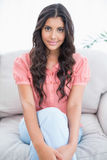 Content cute brunette sitting on couch looking at camera Stock Photography