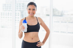 Content dark haired model in sportswear drinking water Stock Photos