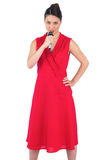 Content elegant brunette in red dress holding microphone Stock Photos