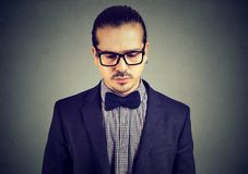 Calm young man posing on gray. Content elegant man in eyeglasses looking down in sorrow posing on gray backdrop royalty free stock image