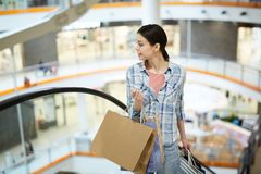 Enjoyable lady choosing stores for shopping. Content enjoyable young lady in casual clothing holding paper bags and looking around while choosing stores for royalty free stock image