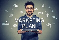 Content entrepreneur having marketing plan. Young cheerful hipster man holding tablet excited with successful marketing plan looking at camera stock photo