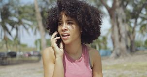 Content ethnic woman speaking on phone stock footage