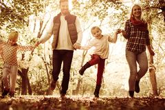 Content family jumping trough park. Family spending day in park stock image
