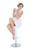 Content fashion blonde model posing sitting on bar chair Stock Images