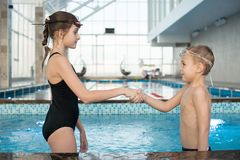 Confident junior swimmer greeting each other in pool royalty free stock photo