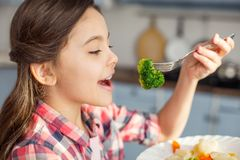Content girl eating healthy vegetables for breakfast Royalty Free Stock Photos