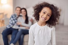 Content girl and her in the background. Happy life. Nice alert curly-haired girl smiling and her sitting on the couch and hugging in the background Stock Photography