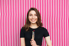 Content girl with paintbrushes. Portrait of woman in casual clothing posing on striped background with paintbrushes Stock Photo