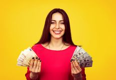 Content girl with piles of money. Young smiling woman excited with win and showing dollar and euro bills smiling at camera on yellow background royalty free stock image