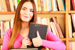 Content girl student in college library. Education school concept. Content female student fashion long hair girl in college library giving thumb up gesture of Royalty Free Stock Photography