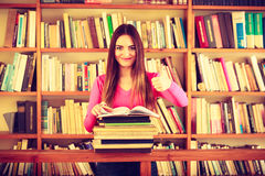 Content girl student in college library. Education school concept. Content female student hipster long hair girl in college library giving thumb up gesture of Stock Image