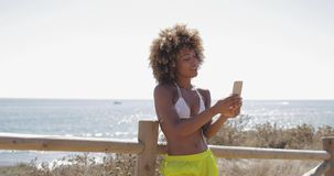 Content girl taking selfie on beach. Wonderful young ethnic girl in swimsuit using smartphone and posing for selfie on background of tropical ocean coastline stock footage