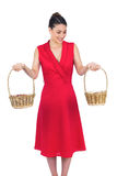Content glamorous model in red dress holding baskets Stock Photography