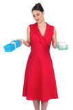 Content glamorous model in red dress offering presents Royalty Free Stock Photos