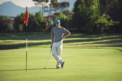 Content golfer. Relaxed golfer standing on green with putter at sunset while playing 18th hole Royalty Free Stock Photos